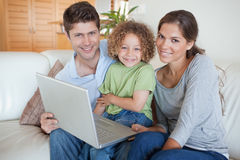 Happy family using a laptop. In their living room Stock Photos