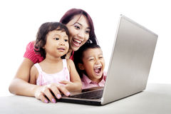 Happy family using laptop. Happy young mother with her children using ultrabook laptop computer Royalty Free Stock Photo