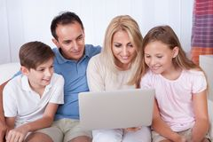 Happy Family Using Laptop. A Happy Family With Two Children Sitting On A Sofa Using Laptop At Home Royalty Free Stock Image
