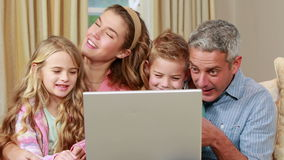 Happy family using laptop on the couch. In high quality 4k format stock video footage