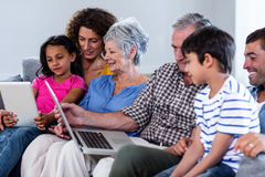 Happy family using laptop and digital tablet in living room Stock Images