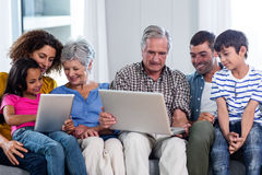 Happy family using laptop and digital tablet in living room Royalty Free Stock Photos