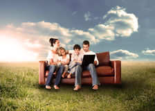Happy family using the laptop in a field. Happy family in the couch using the laptop in a sunny field in the countryside Royalty Free Stock Image