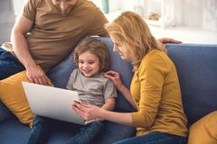 Happy family is using laptop at home. Grinning mommy and dad are showing something interesting to their son on computer screen. Little boy is smiling while Stock Images