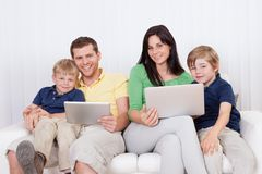 Happy family using laptop at home Stock Photography