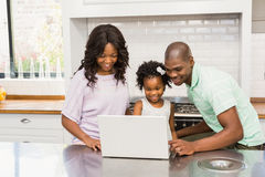 Happy family using laptop. In the kitchen Royalty Free Stock Image