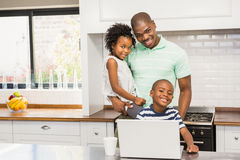 Happy family using laptop. In the kitchen Royalty Free Stock Images