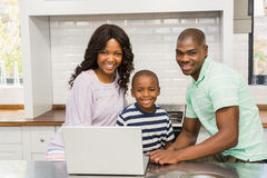 Happy family using laptop. In the kitchen stock image