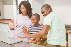 Happy family using laptop. In the kitchen stock images