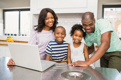 Happy family using laptop. In the kitchen stock photography