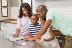 Happy family using laptop. In the kitchen stock photos