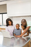 Happy family using laptop. In the kitchen royalty free stock photos