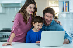 Happy family using laptop. At kitchen royalty free stock photography