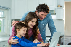 Happy family using laptop. At kitchen stock photo