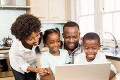 Happy family using laptop in the kitchen. At home stock images
