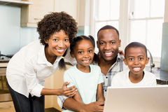 Happy family using laptop in the kitchen Royalty Free Stock Photography