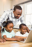 Happy family using laptop in the kitchen. At home royalty free stock photo