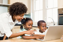 Happy family using laptop in the kitchen. At home royalty free stock image