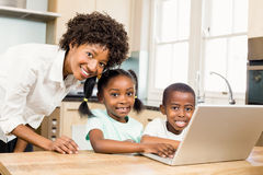 Happy family using laptop in the kitchen. At home royalty free stock images