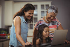 Happy family using laptop in kitchen Royalty Free Stock Images