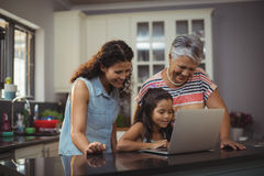 Happy family using laptop in kitchen Royalty Free Stock Photos