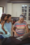 Happy family using laptop in kitchen Stock Image