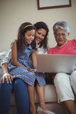 Happy family using laptop in living room Stock Image