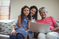 Happy family using laptop in living room. Portrait of happy family using laptop in living room at home Stock Photography