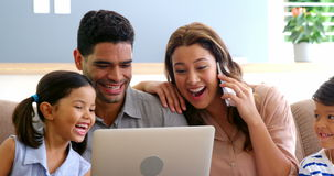 Happy family using laptop, mobile phone, digital tablet in living room. At home stock footage