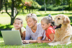 Happy family using laptop in the park Royalty Free Stock Image