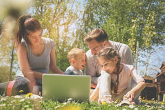 Happy family using laptop, sitting on the green grass. Family enjoying on the meadow in the spring day Stock Photo