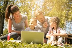 Happy family using laptop, sitting on the green grass. Family en royalty free stock images