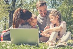 Happy family using laptop, sitting on the green grass. Family en royalty free stock photos