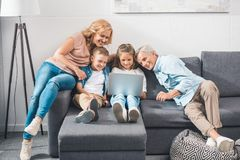 Family using laptop. Happy family using laptop while sitting on sofa at home Royalty Free Stock Photos