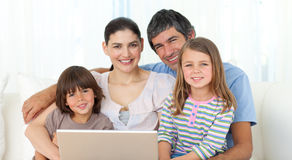 Happy family using a laptop on the sofa. Smiling at the camera Stock Image