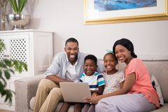 Happy family using laptop on sofa at home. Portrait of happy family using laptop on sofa at home stock image