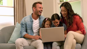 Happy family using laptop on the sofa. Happy family using laptop together on the sofa in slow motion stock footage