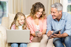 Happy family using laptop, tablet and smartphone Royalty Free Stock Images