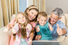 Happy family using laptop with thumbs up Royalty Free Stock Images