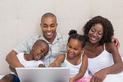 Happy family using laptop together on bed Stock Photos