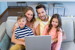 Happy family using the laptop together. At home in the living room Royalty Free Stock Photo