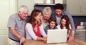 Happy family using laptop together. In the kitchen stock video footage