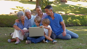 Happy family using laptop together in the park. On a sunny day stock footage