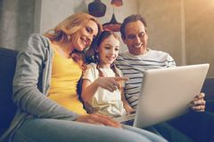 Happy family using laptop together. There is no place like home. Low angle shot of a positive three members family embracing while sitting on a sofa at their Stock Photography