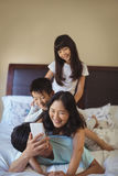 Happy family using mobile phone in the bed room Royalty Free Stock Photography