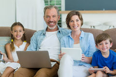 Happy family using mobile phone, digital tablet and laptop in living room Stock Image