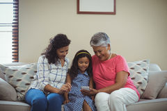 Happy family using mobile phone in living room Stock Image