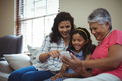Happy family using mobile phone in living room Royalty Free Stock Photo