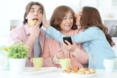 Happy family using mobile phone together Royalty Free Stock Image