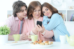 Happy family using mobile phone together Royalty Free Stock Photos